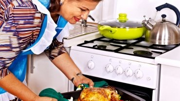Woman taking baked chicken out of the oven.