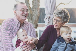 Elderly-parents-holding-grandchildren
