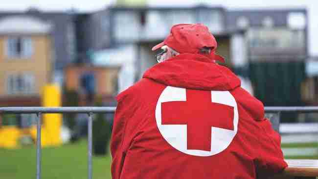 senior elderly man's back with a red hoodie on with a red cross on it and he is always wearing a red hat
