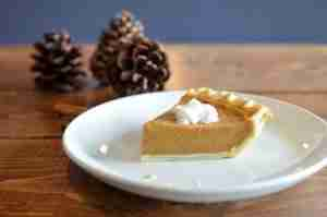 Pumpkin pie on a white plate next to pine cones