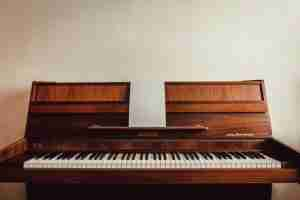 brown piano against a white wall