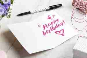 happy birthday written in pink on a card