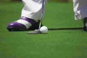 Purple golf shoes putter and golf ball on green grass