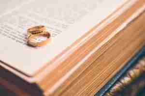 two gold wedding bands on bible