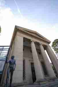 front of a museum building with a statue