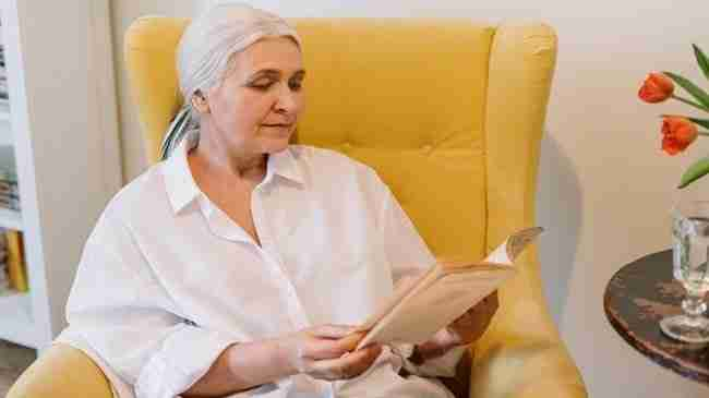 elderly aged woman sitting on a yellow chair reading an book