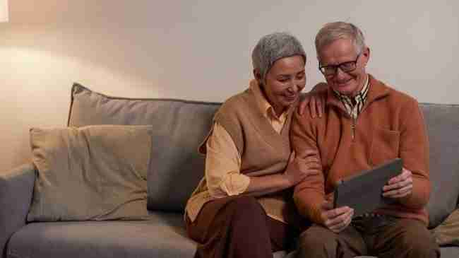 grandparents sitting on a couch ooking and smiling at a tablet in their hands