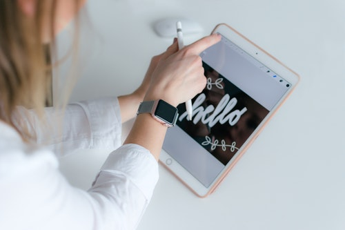 Woman on tablet writing hello in fancy font