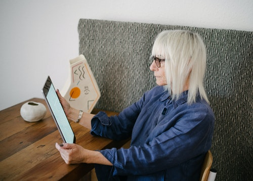 older woman with white hair reading on tablet at a table while sitting