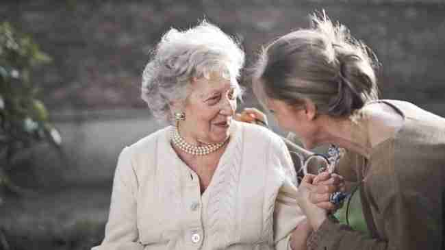 one elderly senior woman and one imddle aged woman sitting on a bench outside smiling and laughing holding onto each others hand