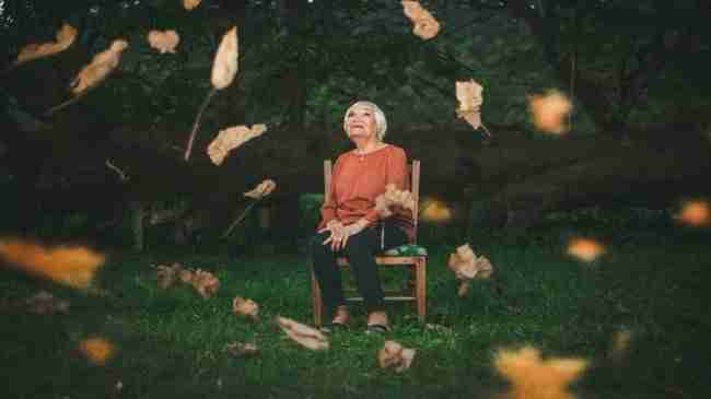 senior woman sitting on a chair in the middle of grass while autumn colored leaves fall down around her