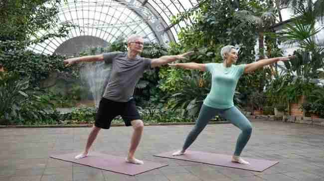 older man and woman standing on yoga mats doing yoga stretches outside