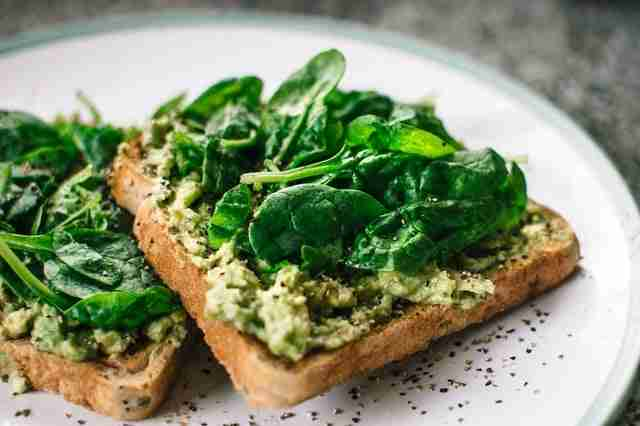 two pieces of avocado toast on a plate covered in spinach, pepper, and other spices
