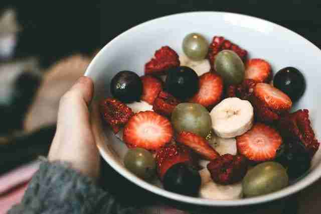 person holding a bowl of fruit salad made from raspberries, strawberries, bananas, and green and purple grapes