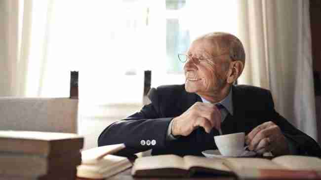 elderly man smiling sitting at a table at home while sipping on a coffee and reading a book