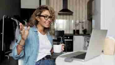 woman smiling while sitting down at a kitchen table ehile on a video meeting on the laptop