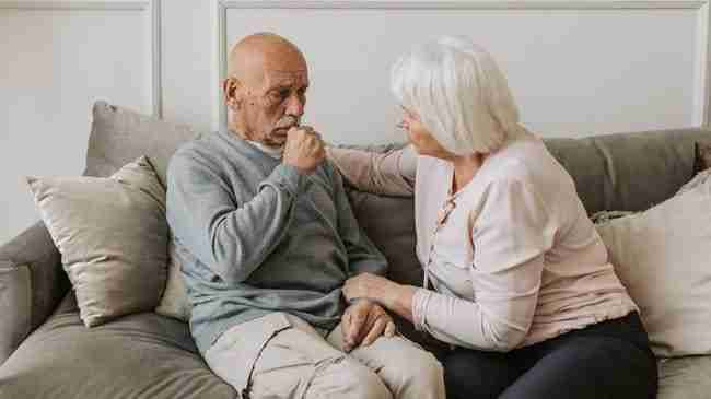 elderly man and woman sitting on the couch